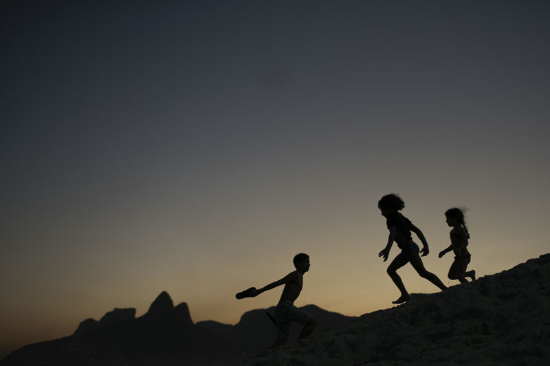 Children are silhouetted against the setting sun as they run on the sand at Ipanema beach in Rio de Janeiro, Brazil, Aug 1, 2016. Photo: AP/File
