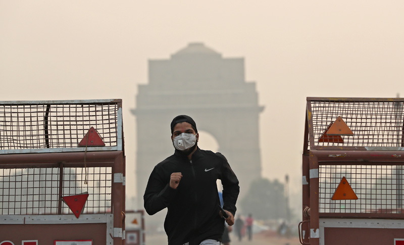 A man wearing a mask runs past the India Gate on a smoggy morning in New Delhi, India, October 28, 2019. Photo: Reuters
