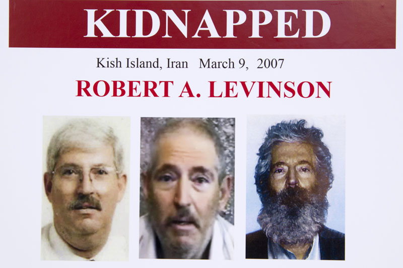 An FBI poster showing a composite image of former FBI agent Robert Levinson, right, of how he would look like now after five years in captivity, and an image, center, taken from the video, released by his kidnappers, and a picture before he was kidnapped, left, displayed during a news conference in Washington, March 6, 2012.  Photo: AP/File