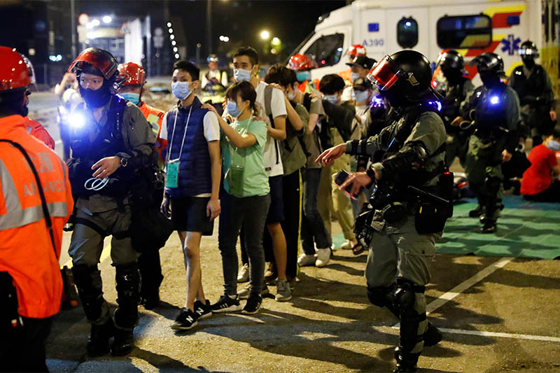 Protesters are escorted by police out of the campus of Hong Kong Polytechnic University (PolyU) during clashes with police in Hong Kong, China November 18, 2019. Photo: Reuters