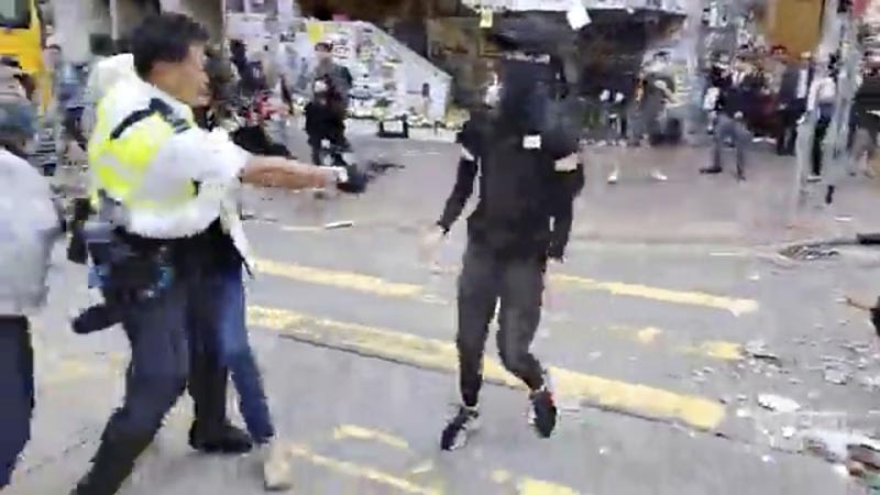 In this image made from video, a police officer, left, prepares to shoot a protester (centre) in Hong Kong Monday, November 11, 2019. Photo: Cupid Producer via AP