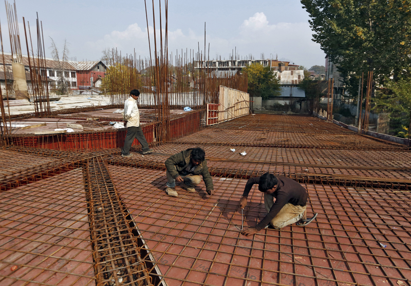 Migrant workers fasten iron rods together at the construction site of a parking lot in Srinagar October 30, 2019. Photo: Reuters