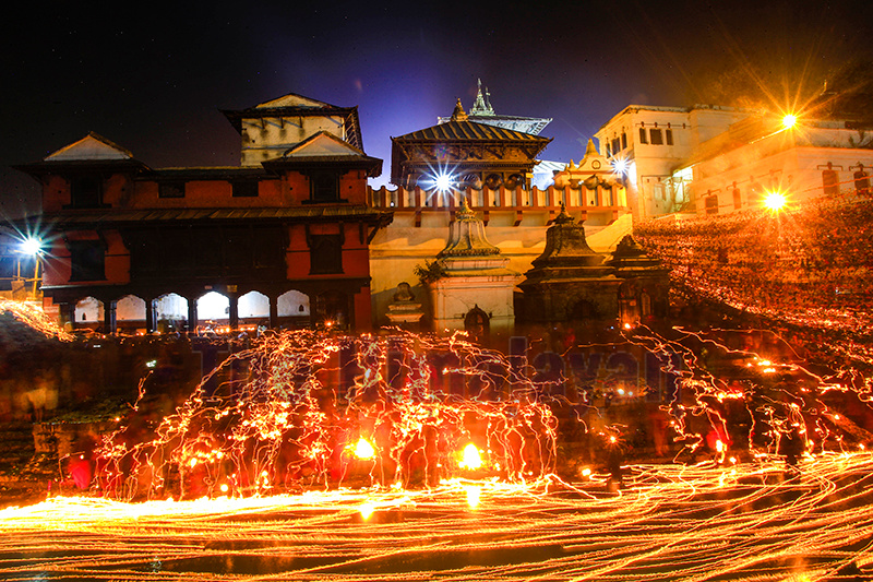 Oil lamps float through the Bagmati River offered as prayer rituals by worshippers in remembrance of their departed beloved ones during Bala Chaturdashi festival at Pashupathinath Temple in Kathmandu, Nepal, on Monday, November 25, 2019. Bala Chaturdashi festival is observed in remembrance of late beloved ones, a belief that by performing rituals the departed souls can secure a better place in heaven. Photo: Skanda Gautam/THT
