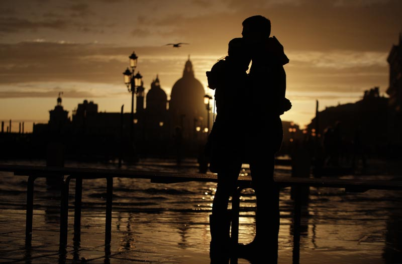 A couple stands in a golden sunset in Venice, Italy, Sunday, November 17, 2019, just hours after an exceptional 1.5 metre tide receded from nearby St Mark's Square. Photo: AP