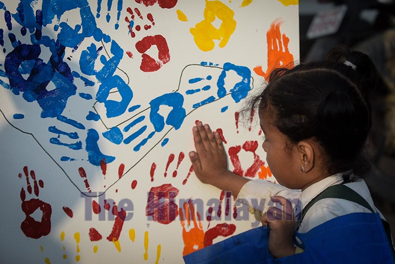 A child leaving the imprint of her palm on canvas to celebrate World Children's Day at Patan Durbar Square, Lalitpur, on Wednesday. Photo: Naresh Shrestha/THT