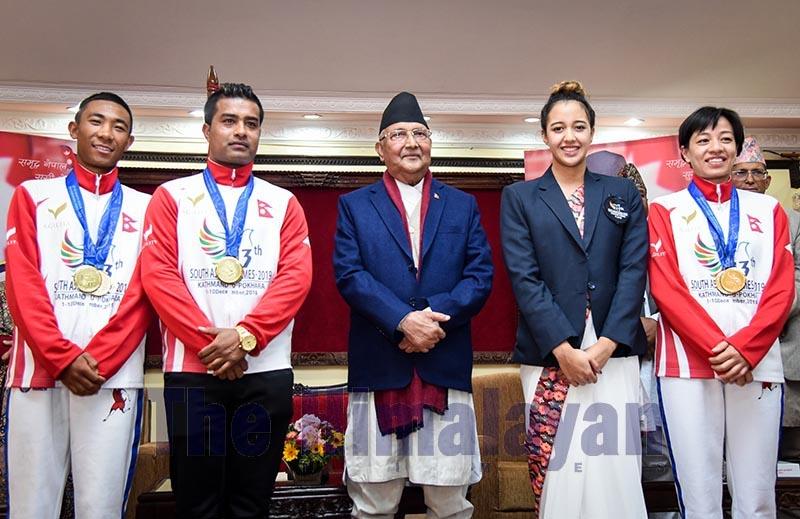 Prime Minister KP Sharma Oli with players who won more than two gold medals at the SA Games, in Kathmandu, on Wednesday, December 11, 2019. (From left) Golfer Subash Tamang, karateka Manday Kaji, swimmer Gaurika and taekwondo player Ayasha.