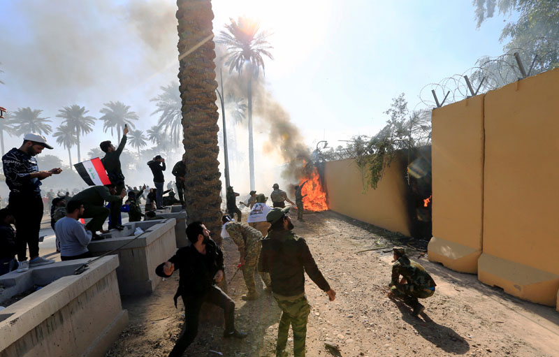 Hashd al-Shaabi (paramilitary forces) fighters set fire on the US Embassy wall to condemn air strikes on their bases, in Baghdad, Iraq December 31, 2019. Photo: Reuters