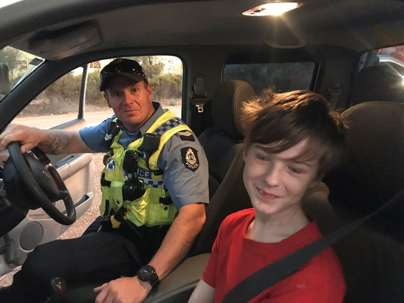 A 12 years old boy sits next to Dalwallinu Police officer S/C Smith after he drove across paddocks to escape the fire in Mogumber, Australia December 15, 2019 in this picture obtained from social media. Photo Credit: Dalwallinu Police va TWITTER via REUTERS