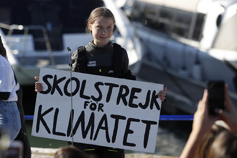 Climate activist Greta Thunberg holds a sign reading 'School strike for the climate' after arriving in Lisbon, aboard the sailboat La Vagabonde, Tuesday, Dec 3, 2019. Photo: AP