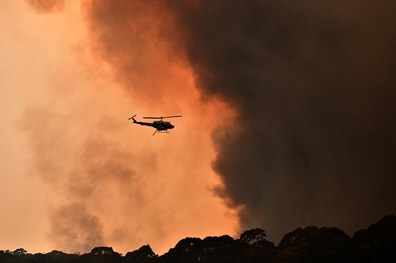 A helicopter is seen during a bushfire near Bilpin, 90 km north west of Sydney, Australia, December 19, 2019. Photo: AAP Image/Mick Tsikas/via Reuters