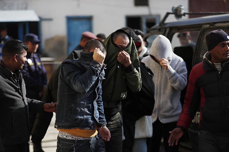 Detained Chinese people cover their faces as they are taken to a court in Kathmandu, on Tuesday, Dec 24, 2019. Photo: AP