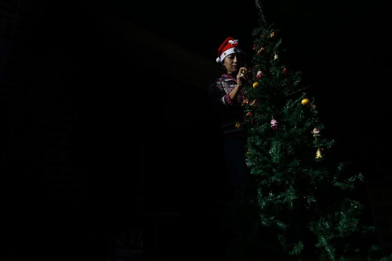 Light illuminates a woman decorating a Christmas tree ahead of Christmas festival, at a cafe in Lalitpur, on Saturday, December 14, 2019. Photo: Skanda Gautam/THT