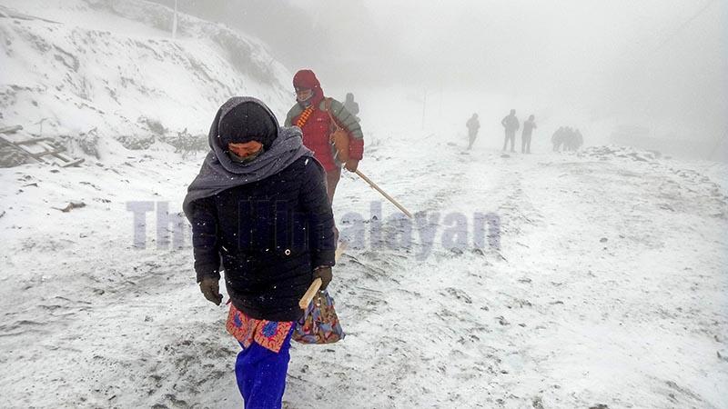 People are seen walking through snow covered road near Kuri, Kalinchowk in Dolakha, on Friday, December 13, 2019. Photo: Gokarna Bhandari/ THT