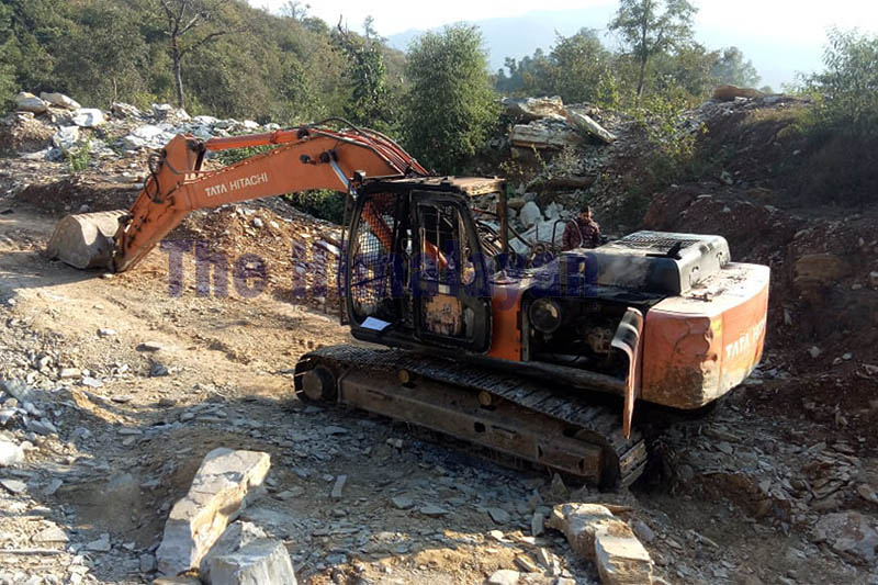 A man looks on at an excavator torched by an unidentified group in Byas Municipality of Tanahun district, on Monday, December 23, 2019. Photo: Madan Wagle/THT