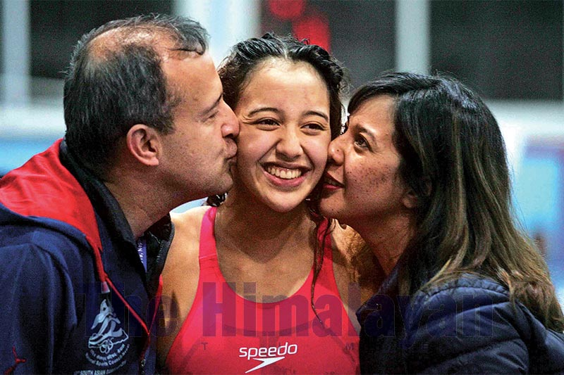 PROUD PARENTS: Paras Singh (left) and Garima Rana kissing their daughter Gaurika Singh after she won the fourth gold medal in 100m freestyle swimming during the 13th South Asian Games in Satdobato, Lalitpur, on Monday, December 9, 2019. Photo: Udipt Singh Chhetry/THT