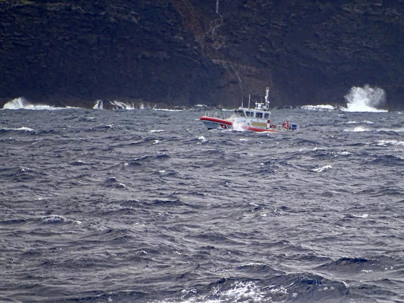 In this photo released by the US Coast Guard, a coast guard vessel searches along the Na Pali Coast on the Hawaiian island of Kauai on Friday, December 27, 2019, the day after a tour helicopter disappeared with seven people aboard. Photo: Lt jg Daniel Winter/US Coast Guard via AP