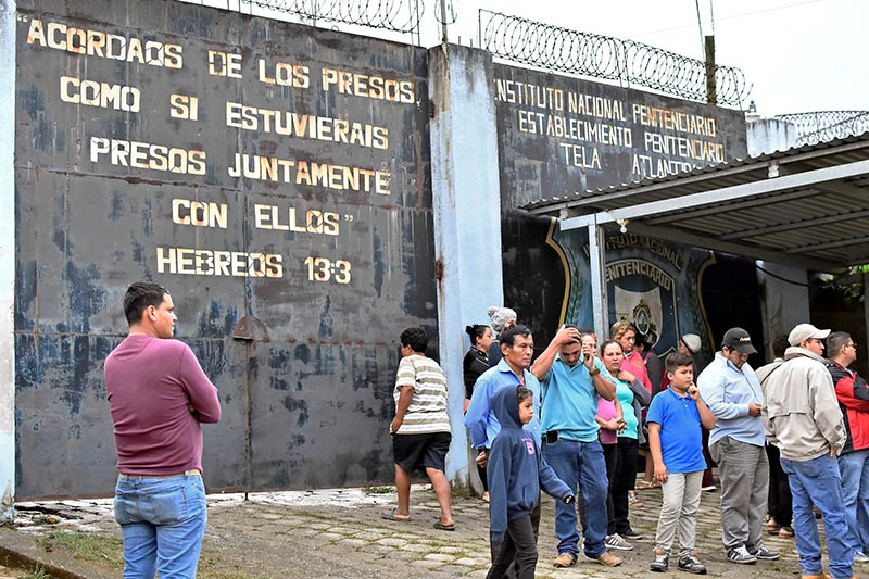 People gather outside the prison after several inmates were killed or wounded during a fight between rival gangs, in Tela, Honduras December 21, 2019. Photo: Reuters