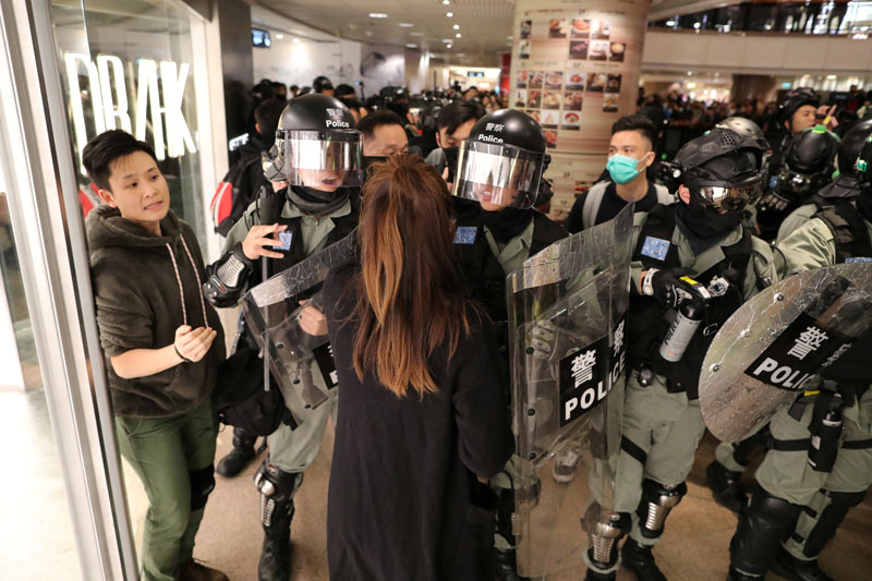 Riot police push back a shopper as Hong Kong protesters march in Harbour City shopping mall in Hong Kong, China, December 21, 2019. Photo: Reuters