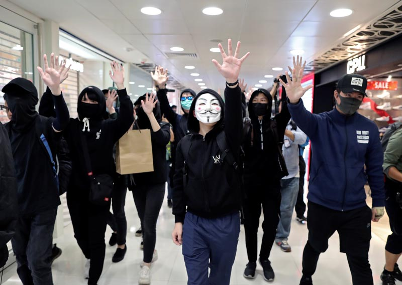 Anti-government demonstrators raise their hands as they walk past shops during a protest in Sheung Shui shopping mall in Hong Kong, China, December 28, 2019. Photo: Reuters