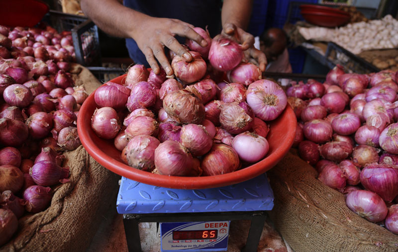 A vendor weighs onions for a customer at a farmers market in Bangalore, India, Tuesday, Dec 3, 2019. Photo: AP