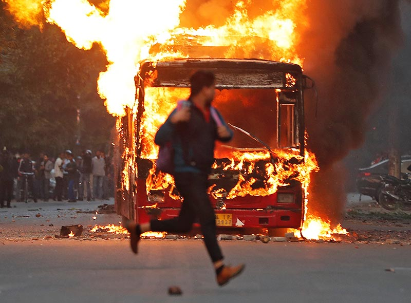 A man runs past a burning bus that was set on fire by demonstrators during a protest against a new citizenship law, in New Delhi, India, on Sunday, December 15, 2019. Photo: Reuters