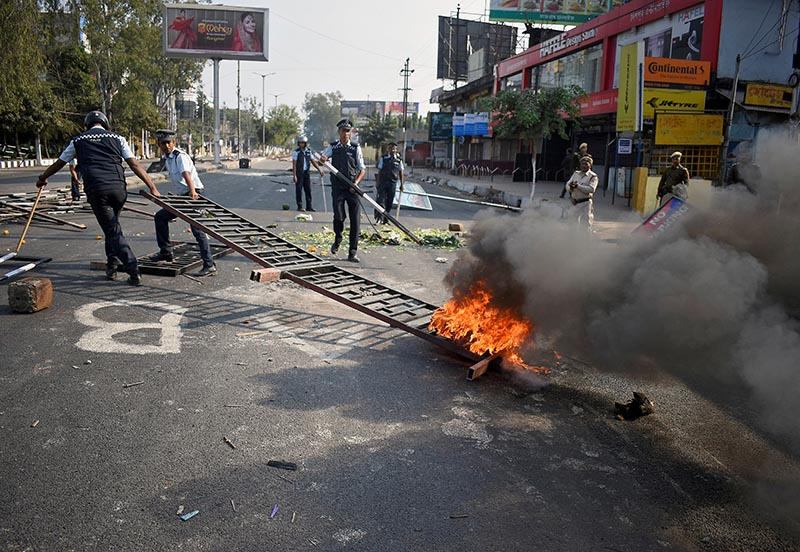 Police remove a burning barricade that was set on fire by demonstrators during a protest after India's parliament passed a Citizenship Amendment Bill, in Guwahati, India, on Thursday, December 12, 2019. Photo: Reuters
