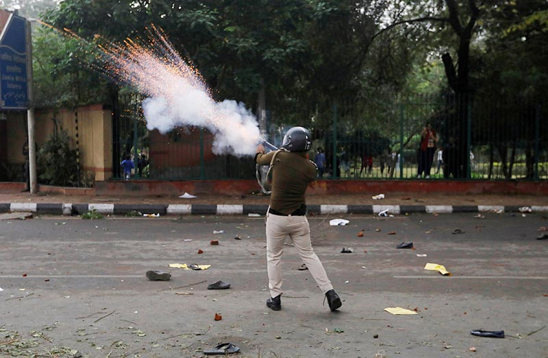 A police officer fires a teargas shell towards protestors during a protest against the Citizenship Amendment Bill, a bill that seeks to give citizenship to religious minorities persecuted in neighbouring Muslim countries, outside the Jamia Millia Islamia University in New Delhi, India, on December 13, 2019. Photo: Reuters