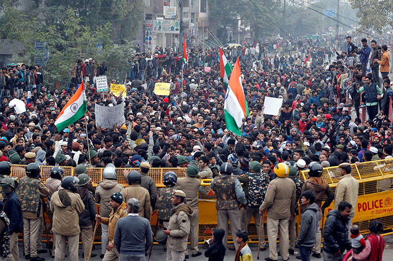 Demonstrators gather behind a police barricade during a protest against a new citizenship law and to show solidarity with the students of the Jamia Millia Islamia university after police entered the university campus on Sunday following a protest against the law, in Seelampur area of Delhi, India, December 17, 2019. Photo: Reuters