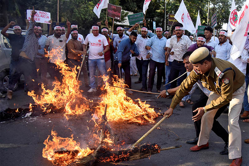 A police officer removes burning effigies that were set on fire by Activists from the All Assam Students Union (AASU) during a protest against the Citizenship Amendment Bill, a bill approved by India's cabinet to give citizenship to religious minorities persecuted in neighboring Muslim countries, in Guwahati, India, December 4, 2019. Photo: Reuters