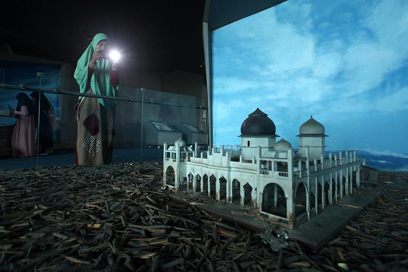 A visitor takes pictures of a miniature of the Baiturrahman Grand Mosque, which was hit by the tsunami, at Aceh Tsunami Museum in Banda Aceh, Indonesia, December 19, 2019. Photo: Reuters