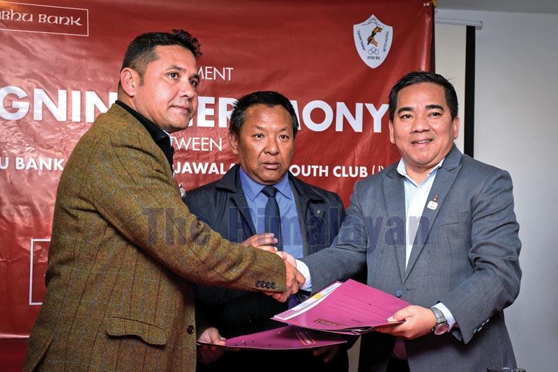JYC President Mahendra Chhetri (left) and Prabhu Bank CEO Ashok Sherchan exchange the MoU as ANFA President Karma Tsering Sherpa (centre) looks on during a signing ceremony in Kathmandu on Sunday, December 15, 2019. Photo: THT