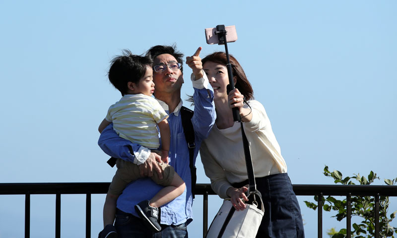 A family takes a selfie photo with a mobile phone at the Beppu Bay Service Area in Beppu, Japan, October 14, 2019. Photo: Reuters