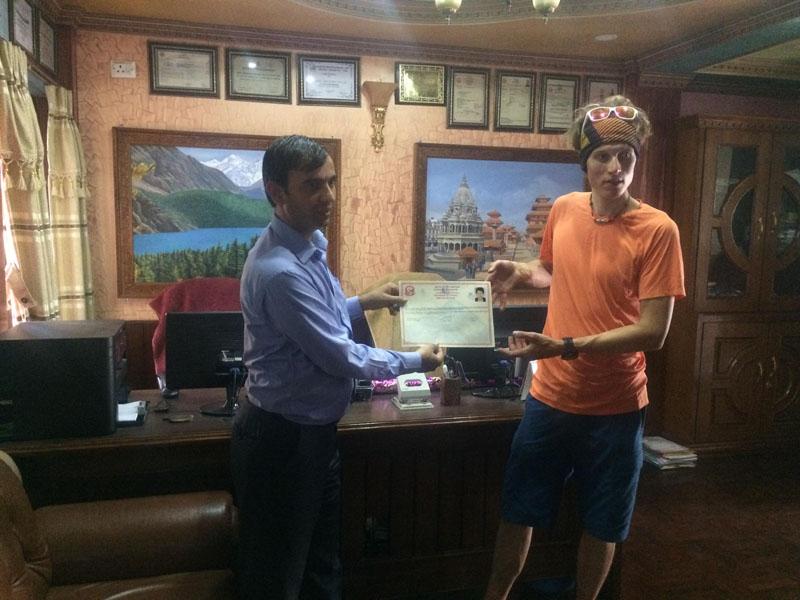 Jost Kobusch, right, receiving the climbing permit from Rishi Bhandari, left.