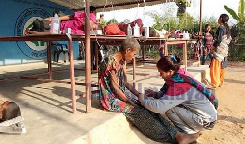 A Sahara Ghar staffer taking care of an elderly person suffering from diarrhoea, in Bardagoriya of Kailali district. Photo: Tekendra Deuba/THT