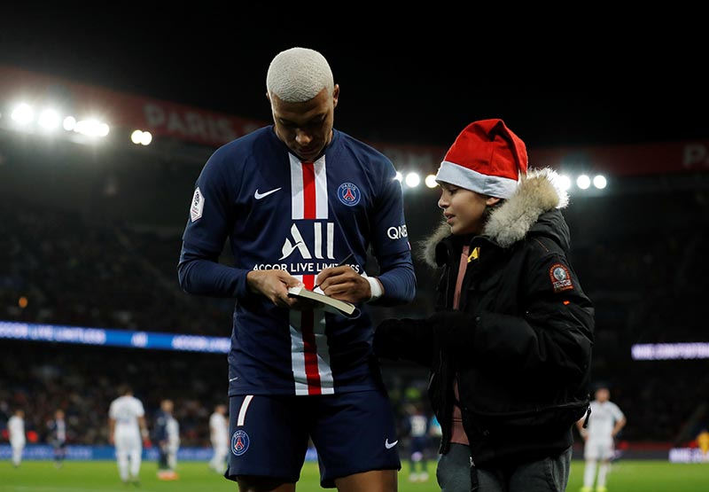 Paris St Germain's Kylian Mbappe with a fan on the pitch during the Ligue 1 match between Paris St Germain and Amiens SC, at Parc des Princes, in Paris, France, on December 21, 2019. Photo: Reuters