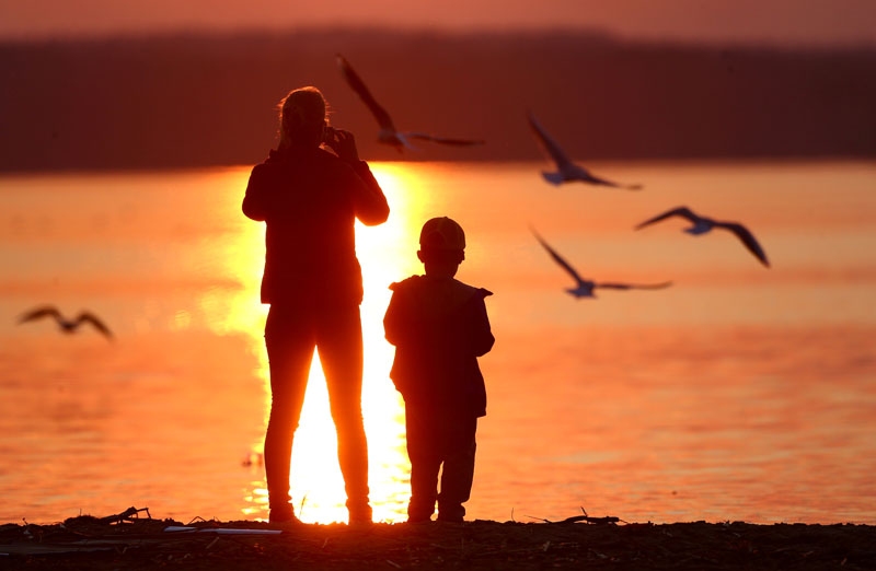 A woman takes a photo during a sunset at a lake on the outskirts of Minsk, Belarus April 2, 2017. Photo: Reuters/File