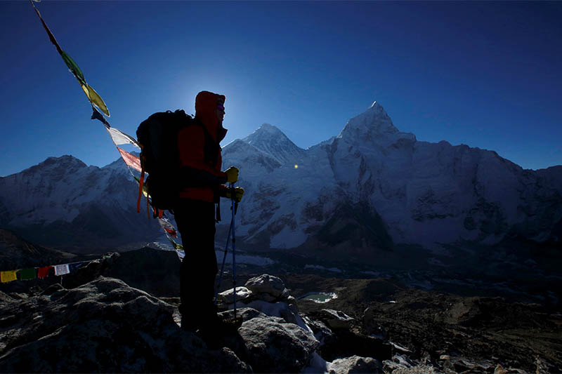 FILE PHOTO: A trekker stands in front of Mount Everest, which is 8,850 meters high (C), at Kala Patthar in Solukhumbu District May 7, 2014. Photo: Reuters