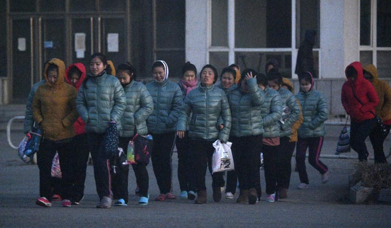 In this December 5, 2019, photo, North Korean factory workers head to work before dawn in Dandong, a Chinese city on the border with North Korea. Photo: Kyodo News via AP