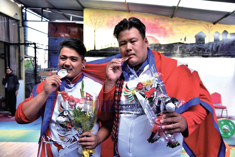 Lifters Sagar Bhandari and Pukar Gurung (right) celebrate after winning medals in the 13th South Asian Games in Pokhara on Sunday, December 8, 2019.Photo: THT