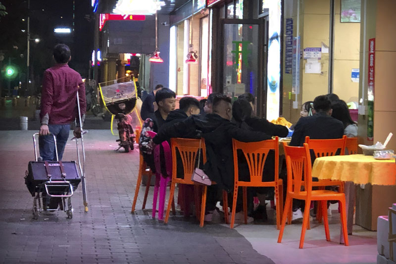 In this Dec. 6, 2019, photo, Wu Yi, who has struggled with Oxycontin abuse, wheels his portable amplifier past customers at an all-night restaurant in Shenzhen in southern China's Guangdong Province. Officially, pain pill abuse is an American problem, not a Chinese one. But people in China have fallen into opioid abuse the same way many Americans did, through a doctor's prescription. And despite China's strict regulations, online trafficking networks, which facilitated the spread of opioids in the U.S., also exist in China. Photo: AP