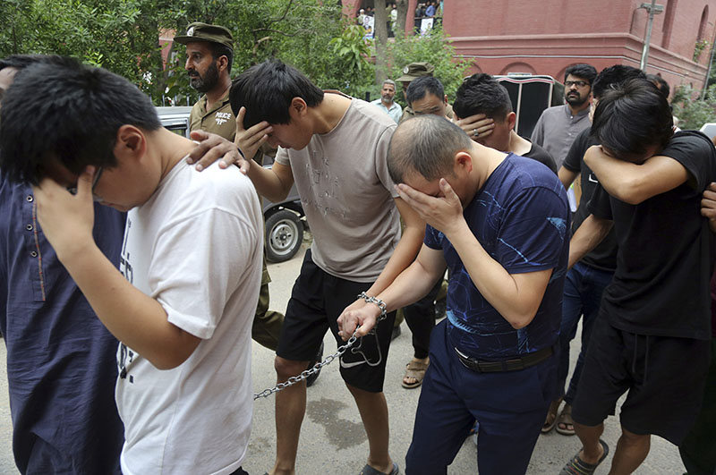 FILE - In this May 11, 2019 file photo, detained Chinese nationals, accused of involvement in a trafficking gang to lure Pakistani women into fake marriages, try to shield their faces while they are escorted by Pakistan's Federal Investigation Agency officers to court in Lahore, Pakistan. Photo: AP