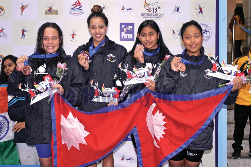 From left Duana Lama, Gaurika Singh, Anushiya Tandukar and Tisha Shakya take photo with national flag and their bronze medals after securing the thrid position in women's 800 metres freestyle relay during the 13th South Asian Games at International Sports Complex Swimming Pool, Satdobato in Lalitpur on Sunday, December 8, 2019. Photo: Udipt Singh Chhetry/THT