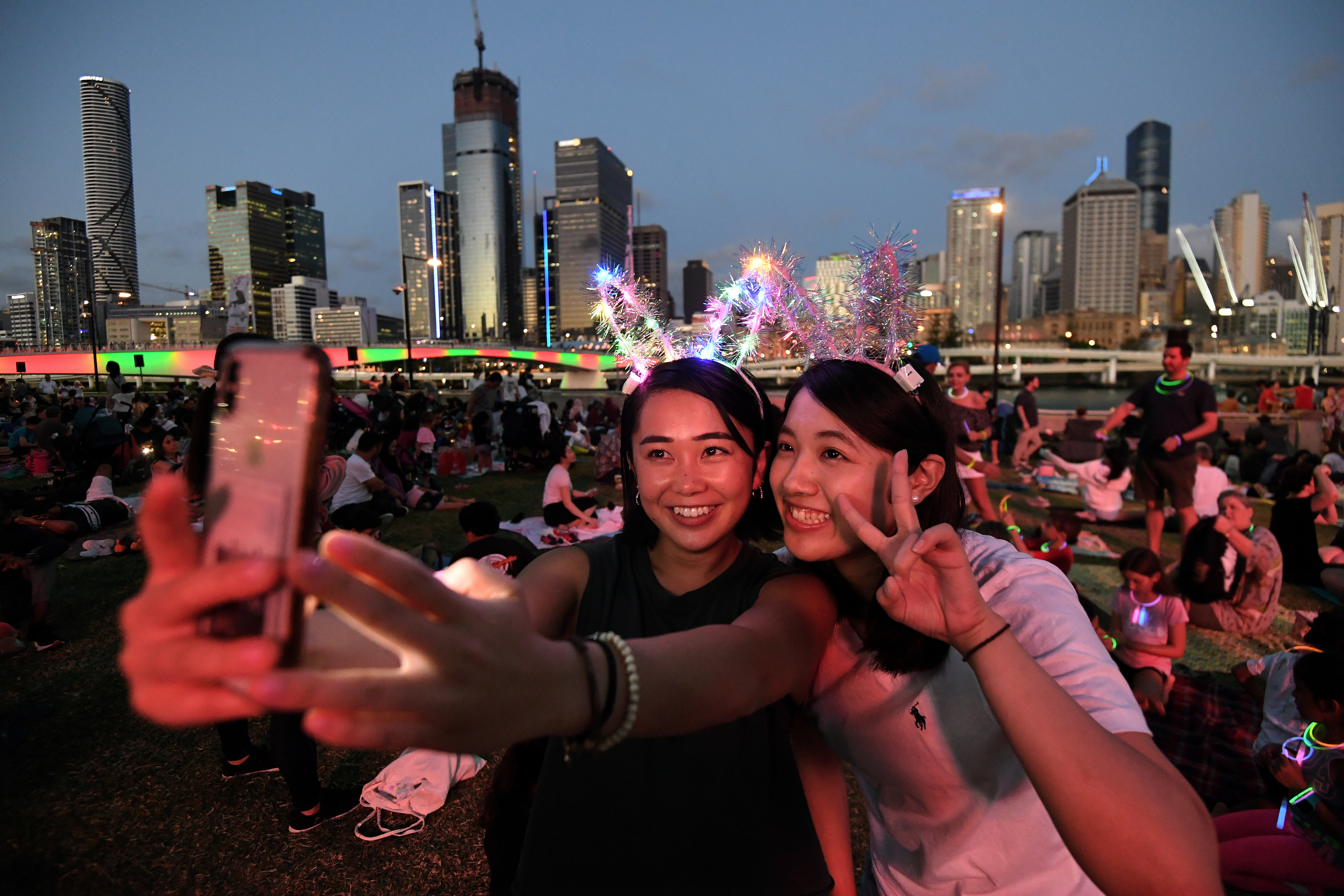 Mizuki (L) and Tsubasa take a selfie as they wait to watch the New Year's Eve fireworks at South Bank in Brisbane, Australia, December 31, 2019. Photo: Reuters
