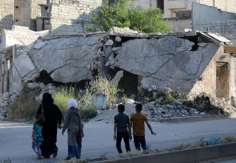 People walk near rubble of damaged buildings in the city of Idlib, Syria May 27, 2019. Photo: Reuters