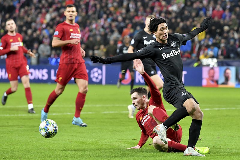 Salzburg's Takumi Minamino (right) is tackled by Liverpool's Andrew Robertson during the group E Champions League soccer match between Salzburg and Liverpool, in Salzburg, Austria, on Tuesday, December 10, 2019. Photo: AP