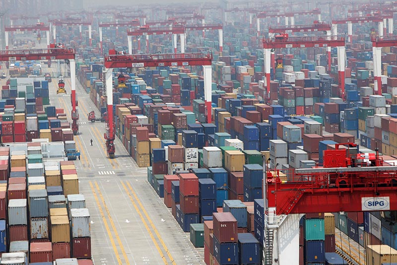 FILE PHOTO: A man walks in a shipping container area at Yangshan Port of Shanghai May 11, 2012. REUTERS/Aly Song/File Photo
