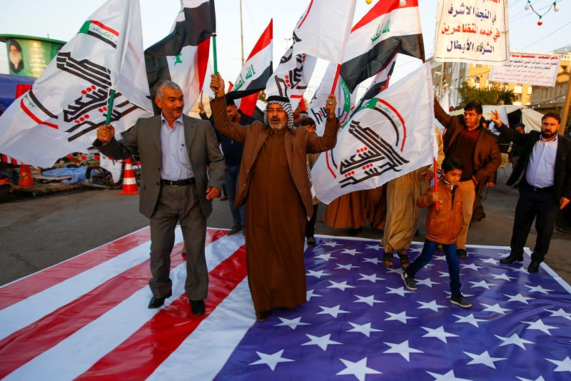 Iraqi people walk on a US flag in a protest after an airstrike at the headquarters of Kataib Hezbollah militia group in Qaim, in the holy city of Najaf, Iraq December 30, 2019. Photo: Reuters