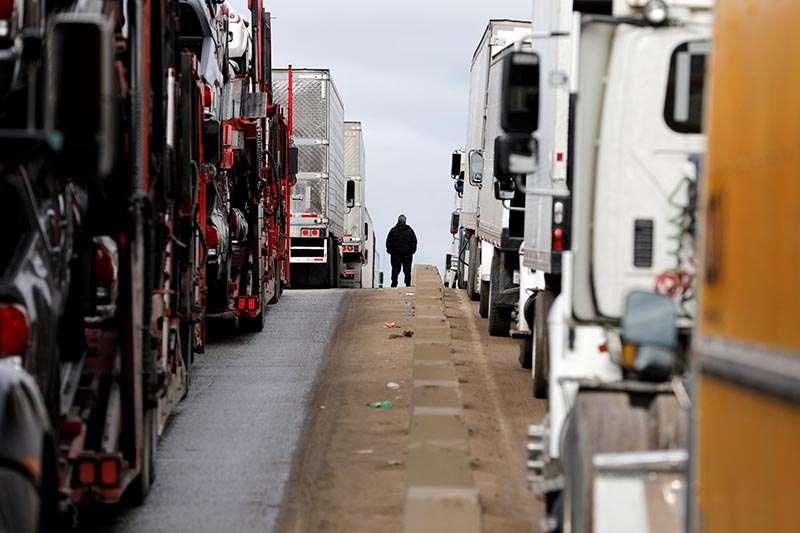 File - A man stands between trucks waiting in a long queue at border customs control to cross into the U.S at the Otay border crossing in Tijuana, Mexico April 3, 2019. Photo: Reuters