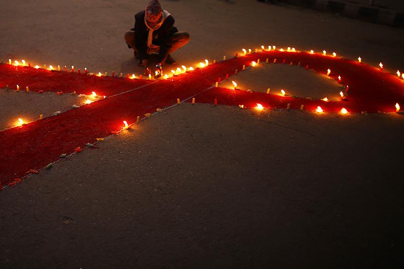 Nepalese people light candles during a candle light program commemorating and marking the 31st World Aids Day organized by Maiti Nepal in Kathmandu, Nepal on Saturday, November 30, 2019. Photo: Skanda Gautam/THT