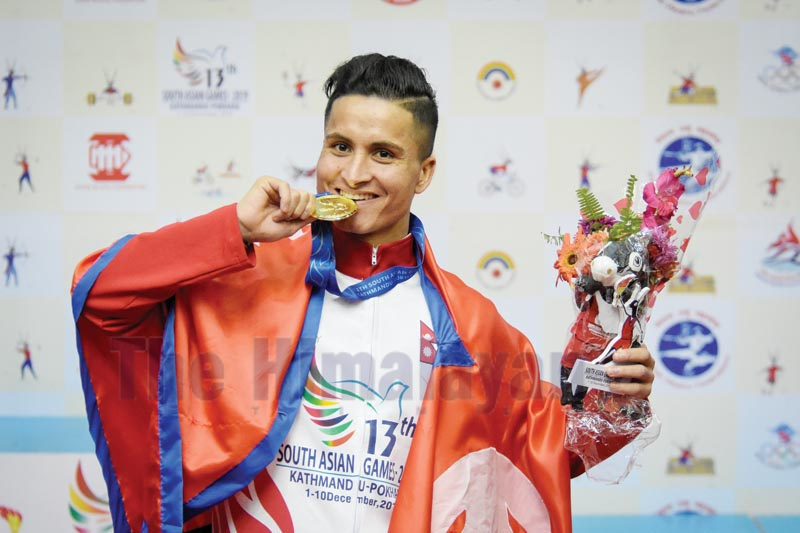 Wushuka Deepak Hamal bites the gold medal after winning a gold medal in the 13th SA Games in Lalitpur on Wednesday, December 5, 2019. Photo: Naresh Shrestha/THT